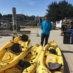 Monterey Bay Kayaks Manager, Sean Furey, stands with kayaks featuring Sea Otter Savvy decals